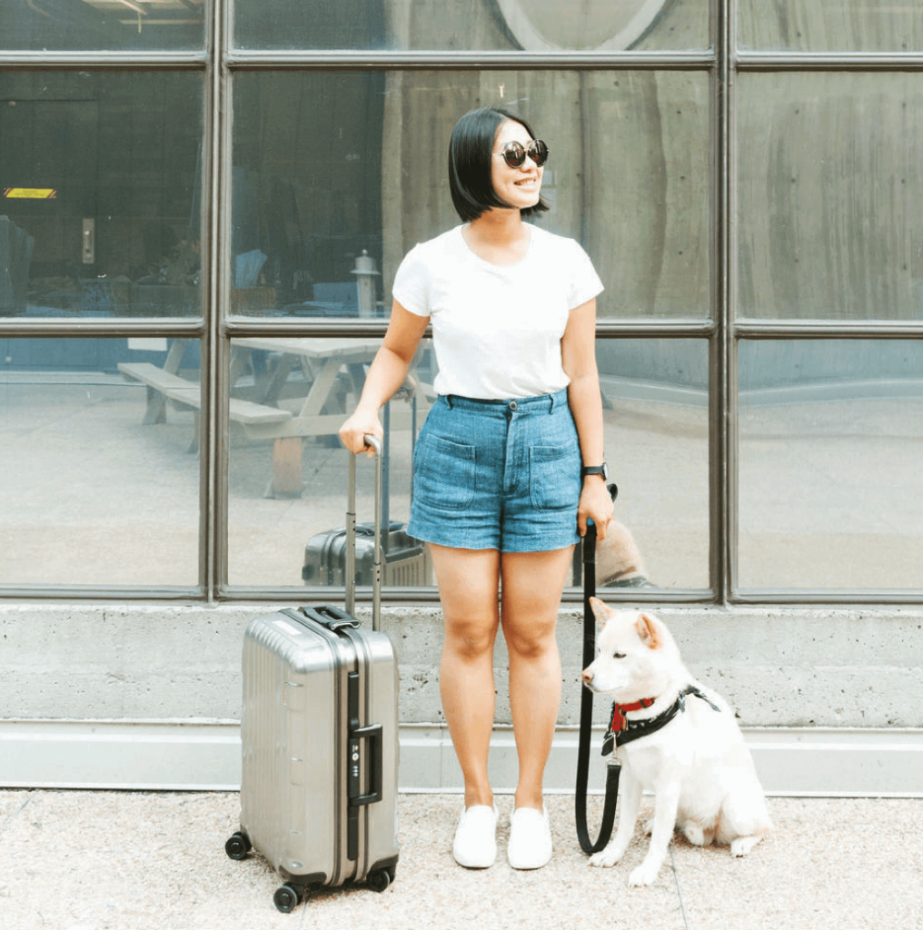 Woman smiling with suitcase and dog